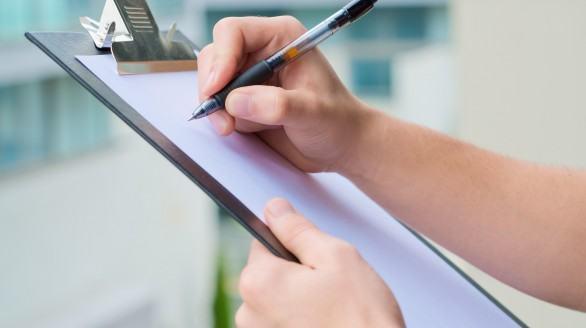 man writing on a clipboard